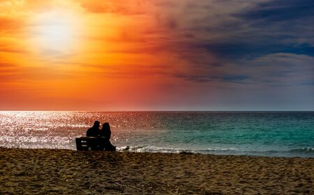 Romantic couple on the beach at colorful sunset on background. Perfect tropical sunset landscape, exotic nature view. Happy romantic couple enjoying beautiful sunset at the beach. Saint Valentine s Day celebration