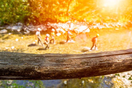 Close up of a wooden handrail in a forest near a river in which a group of persons make trakking in summer on blurred background Banco de Imagens