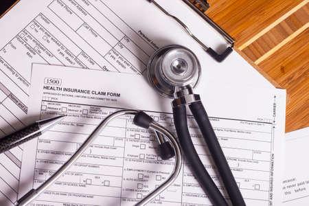 seguro: Estetoscopio y pluma de descanso en una hoja de registros de seguros médicos