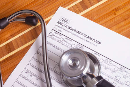 record: Stethoscope and pen resting on a sheet of medical insurance records