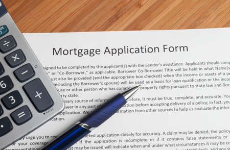 mortgage document: A house key sitting on mortgage application.