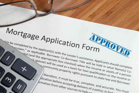 A house key sitting on mortgage application.