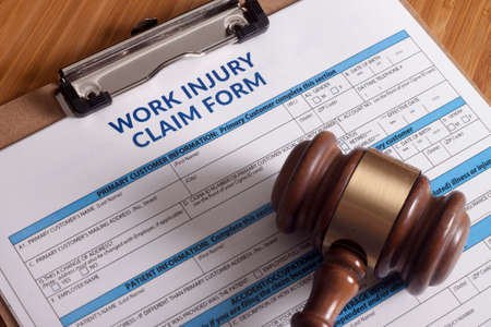 insurance themes: Claim form for a work injury on a desk top