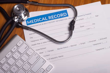 Stethoscope resting on a sheet of medical insurance records Archivio Fotografico