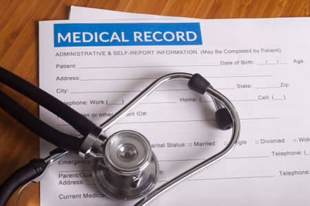 Stethoscope resting on a sheet of medical insurance records Banco de Imagens