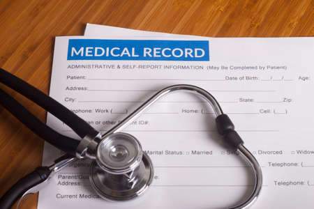 Stethoscope resting on a sheet of medical insurance records Stock Photo
