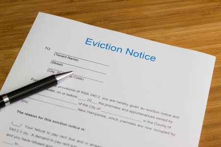 subprime mortgage crisis: Someone filling out Eviction Notice Document Stock Photo