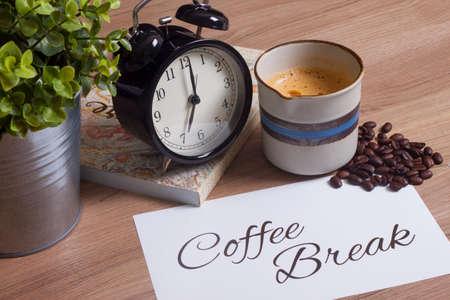 grano de cafe: taza de café, reloj y de cerca cuaderno personal, la hora del café