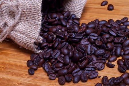 コーヒー バック グラウンド - 木材の背景に対するコーヒー粒の袋
