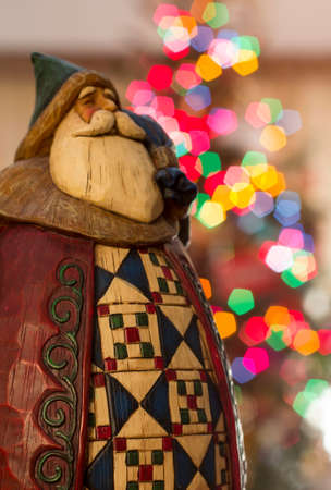 Ceramic Santa Claus figurine in front of a christmas tree Stock Photo