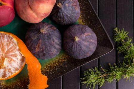 Fruit, Tangerines, Pine, Figs on Black table. Healthy Food Frame Stockfoto