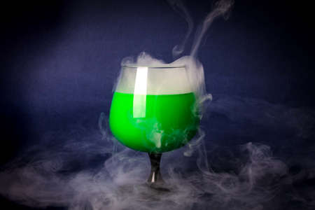 Smoke into cocktail glass on a black background. Witch potion background for Halloween. Unusual bar drink. Stock Photo - 92023038