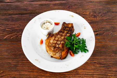 pork chop with vegetables in a white plate
