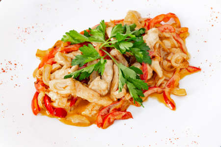 Chicken fricassee with mushrooms on a white plate with vegetables top view close-up Imagens
