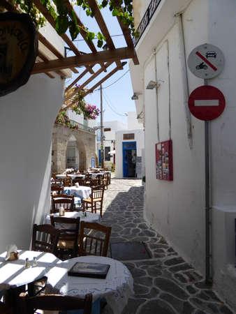 taverna: Tables and chairs line the narrow  streets of Plaka, Milos Island, Greece Editorial