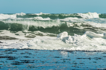 Sea waves hitting on the stones near the coast. White foam comes out of the waves white foam of a sea wave in blue sky 写真素材