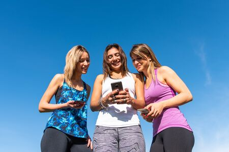 Three happy young women watching the smart phone with a blue sky