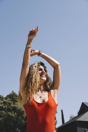Caucasian blond woman coming out of the pool with her arms raised and smiling