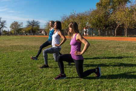 Three Caucasian women in the park, two blondes and one brunette working out in the park. Sport, health and lifestyle concept