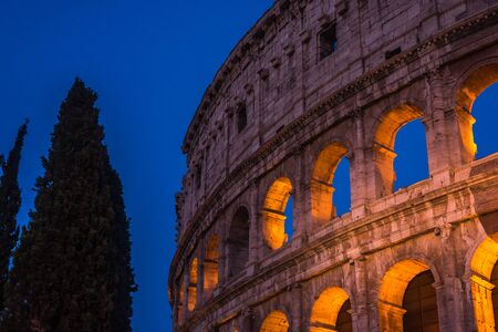The Colosseum under the glow of lights at night, Rome Stock Photo