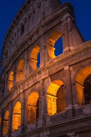The Colosseum under the glow of lights at night, Rome Фото со стока