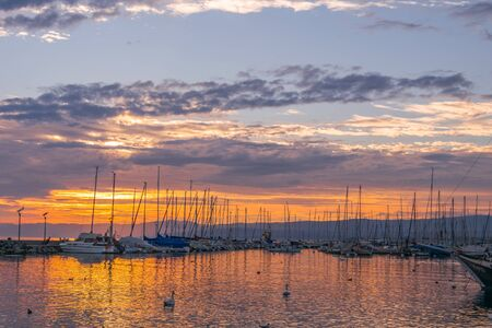 Sunset in Lausanne harbour around the district of Ouchy. Travel concept.