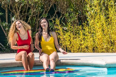 Two beautiful women, one Caucasian and an Asian sitting on the edge of the pool with the gay pride flag in the water. Both talk and smile. LGBT concept