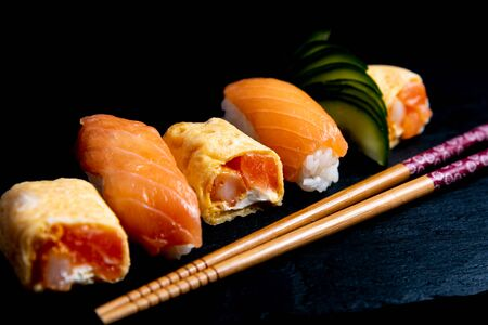 Japanese cuisines nigiri sushi set on black plate served with wasabi, soy sauce. Sushi Roll with salmon, sushi maki roll and tamago sushi on black plate.