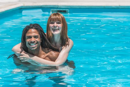 Interracial couple in the pool hugging and smiling