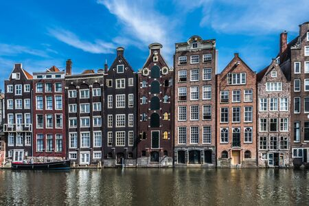 Old canal border houses in typical Dutch architectural style along a main canal in Amsterdam, North Holland, the Netherlands