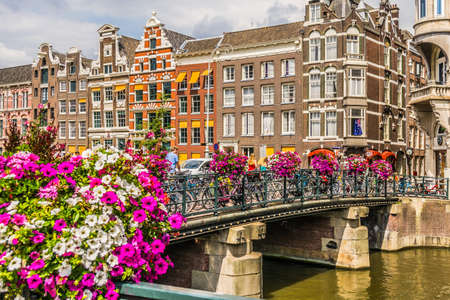 Amsterdam, Netherlands - July 18, 2018: Typical bridge over a canal with many bikes and flowers. 新聞圖片