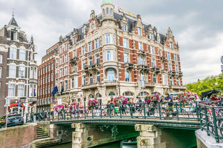 Amsterdam, Netherlands - July 18, 2018: Picturesque traditional Dutch houses and a bridge on the canal. 新聞圖片