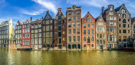 Panoramic view of typical Dutch houses at the Amsterdam canal Damrak in sunny day, Netherlands. High quality photo 版權商用圖片