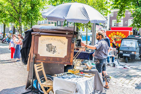 Amsterdam, Netherlands - July 19, 2018: Street photographer is taking pictures of tourists using old analog camera 新聞圖片