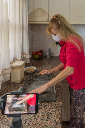 Adult female wearing a face mask to protect from the coronavirus. Shes filmed in her kitchen preparing the cake mould.