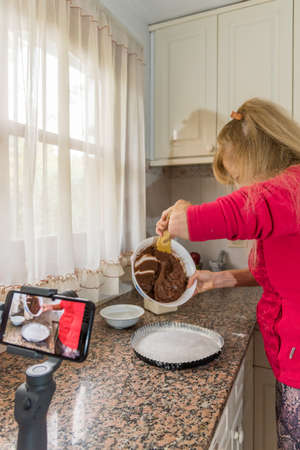 Adult female wearing a face mask to protect herself from the coronavirus. Shes filmed in her kitchen placing the cake mix in the mold. Concept of self-isolation and blogging