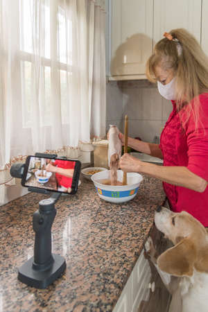 Adult female wearing a face mask to protect herself from the coronavirus. Shes filmed in her kitchen while adding the cake dust. The beagle is gossiping. Concept of self-isolation and blogging
