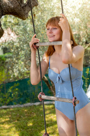 A smiling young woman with red hair in a bathing suit. Shes holding on to a rope ladder on a sunny day. Banque d'images