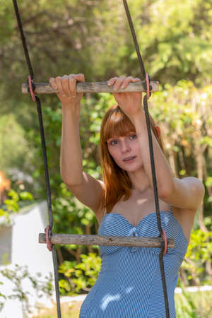 A smiling young woman with red hair in a bathing suit. Shes holding on to a rope ladder on a sunny day. 版權商用圖片