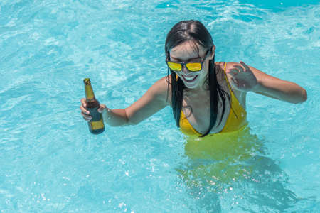 Asian woman in sunglasses dancing with a beer in a pool