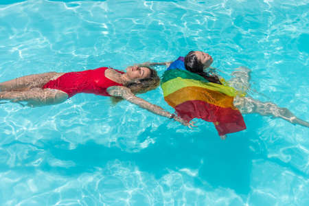 Women floating in a pool with a rainbow flag 版權商用圖片