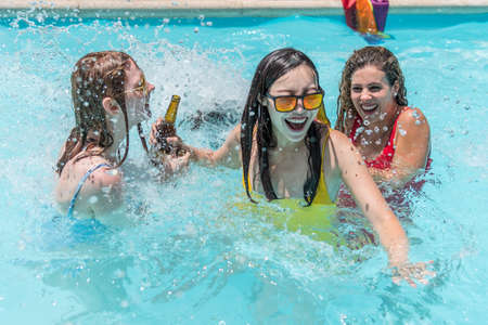 A group of young women from different ethnic groups playing splash around in a pool