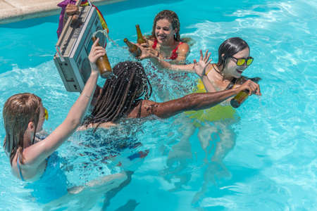 People playing splash around inside a pool with beers while a man carries a cassette player with a rainbow flag