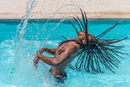 Black man with dreadlocks inside a pool raising his wet hair making a trail of water