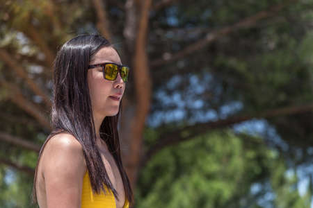 Portrait of an asian woman wearing sunglasses and yellow bathing suit 版權商用圖片