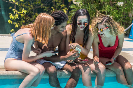 Multiethnic group of people sitting at the edge of a pool using a mobile phone