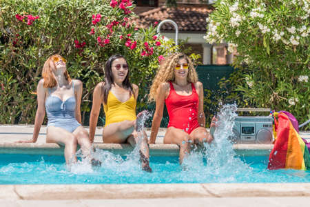 Women of different ethnicities sitting at the edge of a pool splashing the water with their feet 版權商用圖片