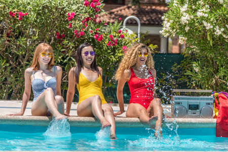 Three women of different ethnicities sitting at the edge of a pool splashing the water with their feet