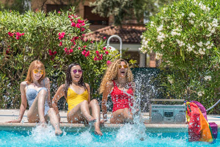 Three women of different ethnicities sitting at the edge of a pool while splashing the water