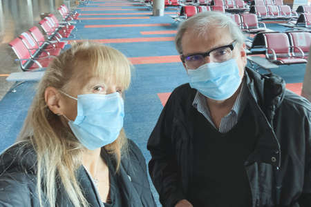 Adult couple taking a selfie at the airport wearing a surgical mask during the covid pandemic. 版權商用圖片